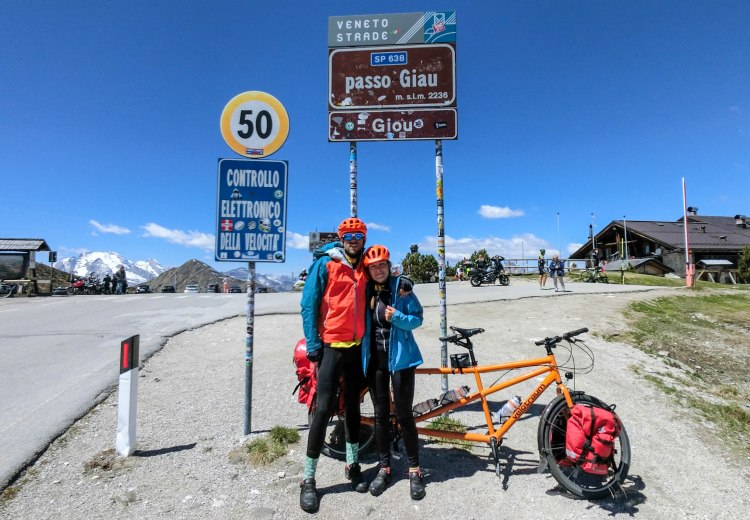 Bicycle couple in front of a tandem bicycle at the Giau pass on their way to the Balkans
