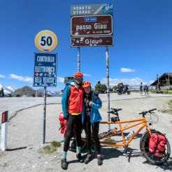 a couple in front of a orange tandem bicycle the passo Giau