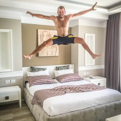 Man jumping on a hotel bed at Te Stela Resort