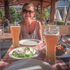 a happy women with sunglasses eating in a restaurant and drinking beer