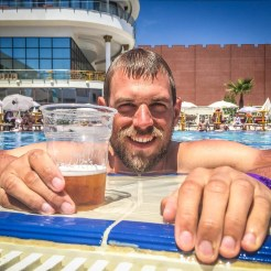 A man drinking beer in swimming pool