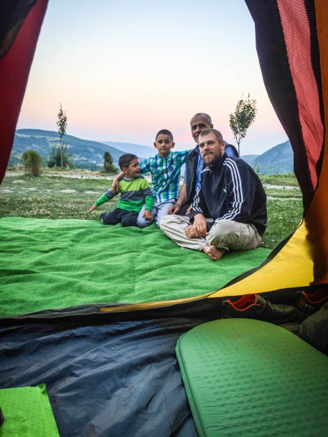 2 men and two children sitting on a sheet in front of a tent in Kosovo, the Balkans