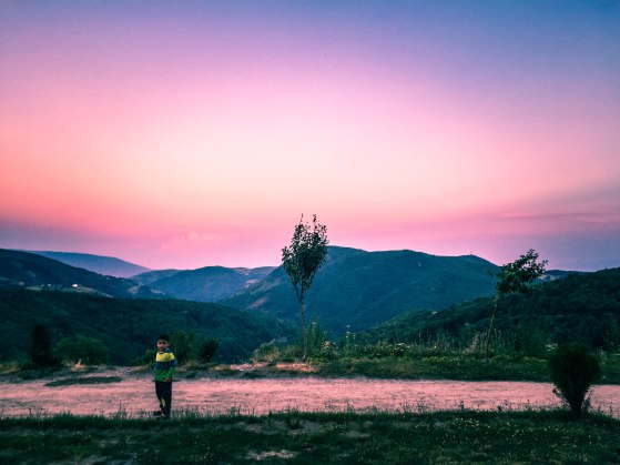 a kid standing in the mountains during a beautiful sunset in Kosovo, in the Balkans