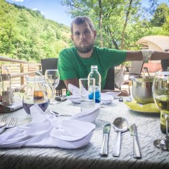 A man drinking apple juice on a set table