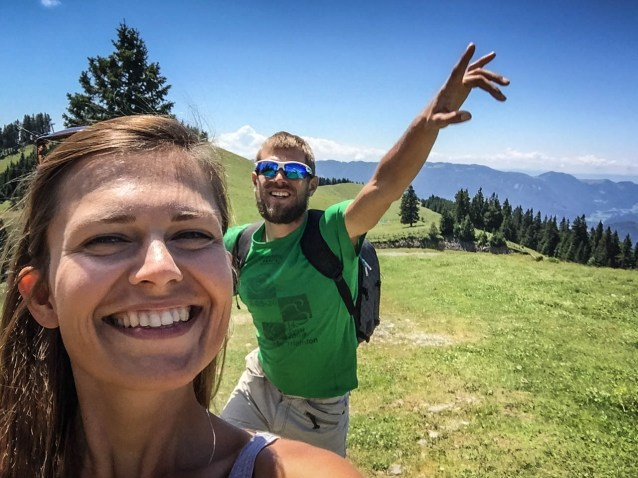 A laughing woman and a man wearing sunglasses greeting in the background in the Slovenian mountains