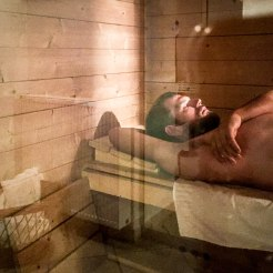 A blonde man laying in the sauna