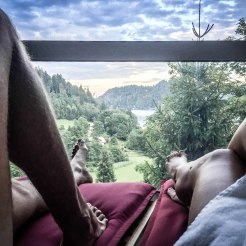 The legs of a man and a woman on a lounger with a great view on a forest