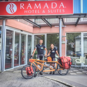 A couple and a tandem bicycle in front of the Hotel Ramada Kranjsk Gora