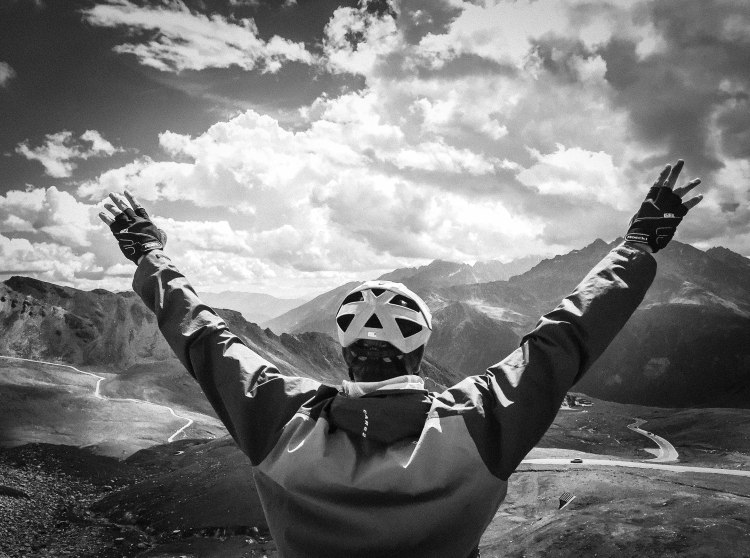 Black and white photo of a male cyclist from the back spreading his arms in the air in the mountains