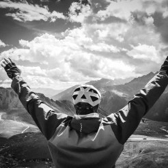 a male bicycle rider celebrates in the mountains