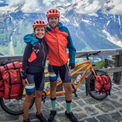 happy couple in front of a tandem bicycle in the mountains