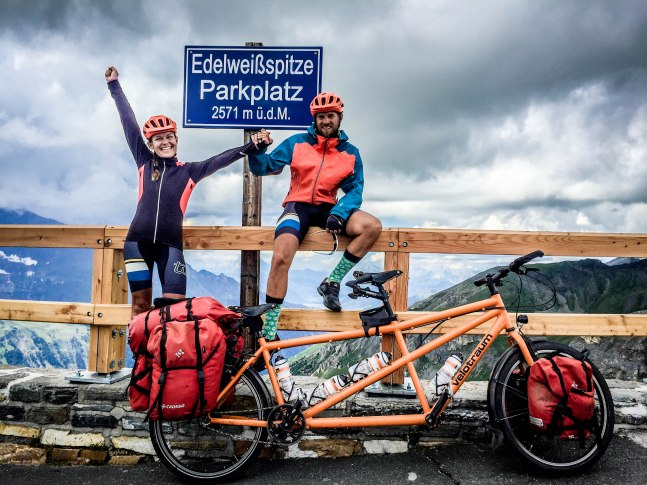 celebrating cycling couple in front tandem bicycle at the Edelweißspitze, Austria