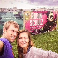 couple in front of Robin Schulz poster