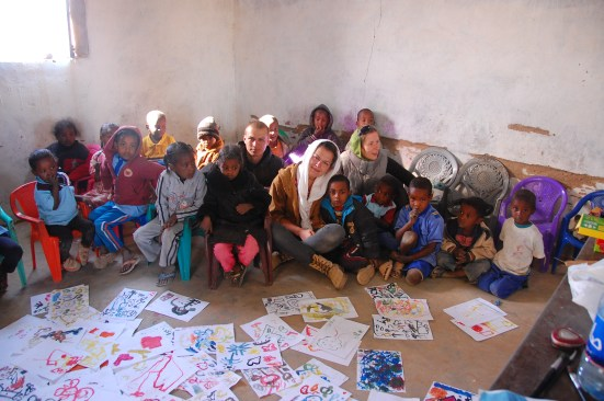 A white woman sitting in on the floor in a school in Sudan with many children