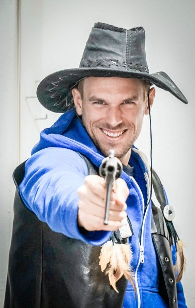 A man with a pistol wearing a cowboy costume