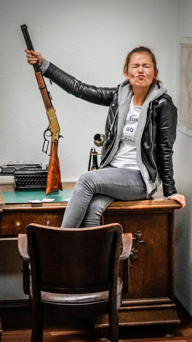 a woman with a gun sitting on a desk