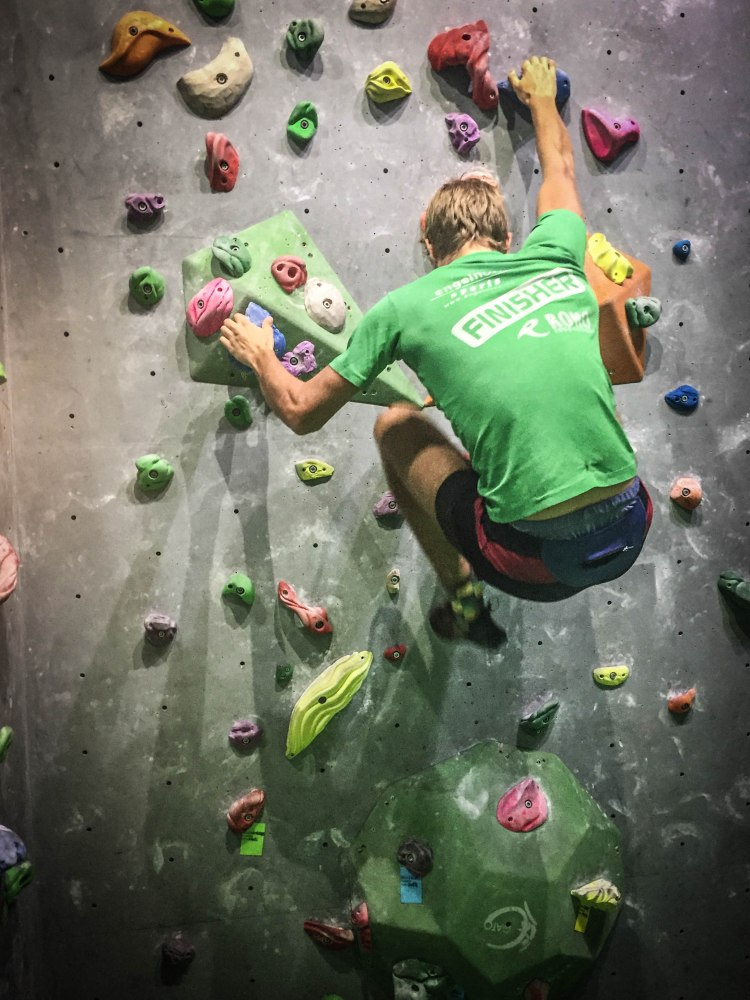 a man with green t-shirt indoor bouldering