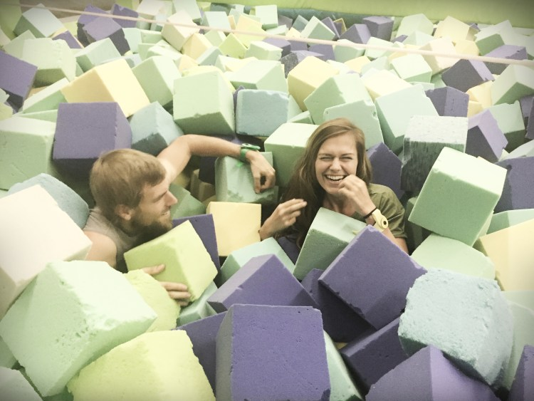 blond man and brunette woman in a foam sea