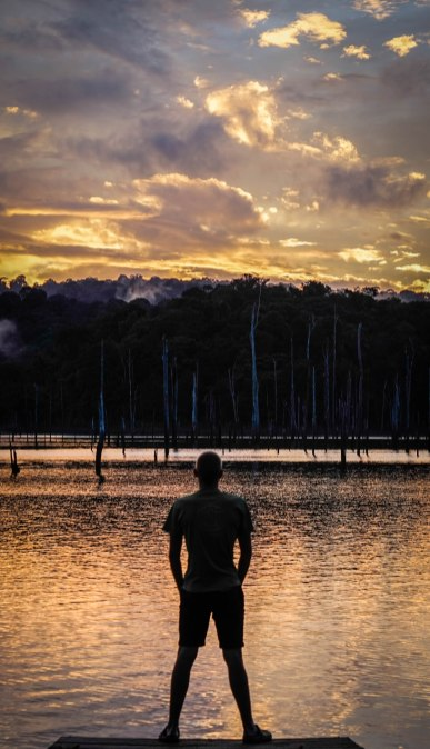 Man standing at a lake during sunset