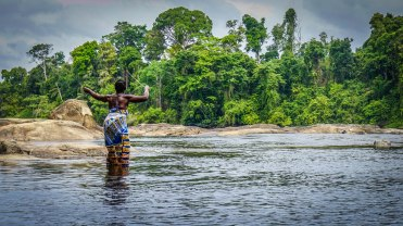 A tribal woman standing in the Suriname rive