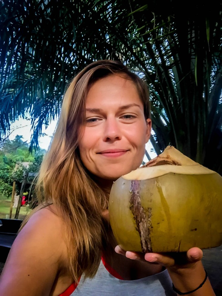 happy woman drinking a coconut