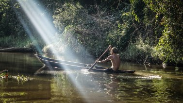 a man on a wooden canoe on a river in Guyana