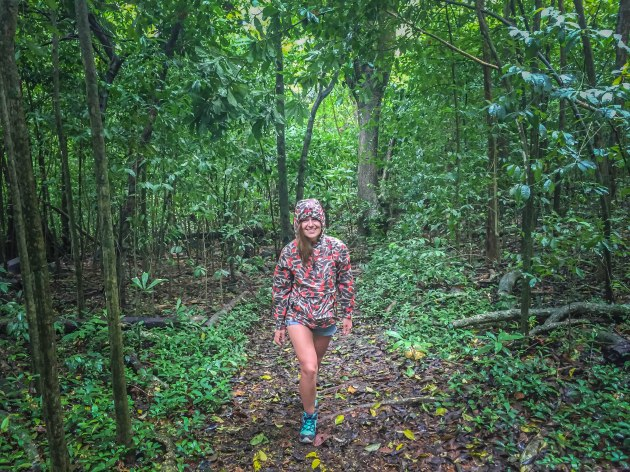 A woman wearing a colorful jacket trekking in the rain forest