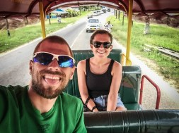 smiling man and woman on a tuk-tuk