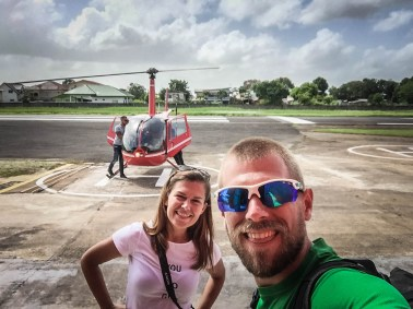 a man and woman in front of a helicopter