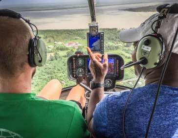 two man in a helicopter cockpit during Paramaribo Helicopter Flight