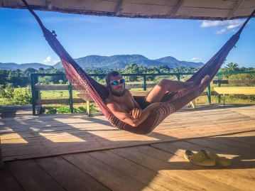 Man with sunglasses laying in a hammock / Cycling through South America
