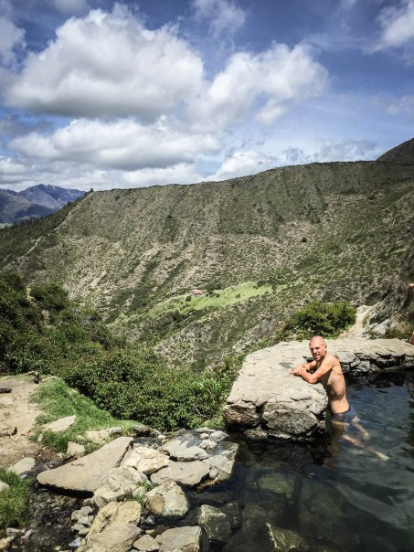a man in a natural pool in the mountains
