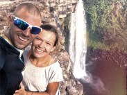man with sunglasses and happy woman at a waterfall