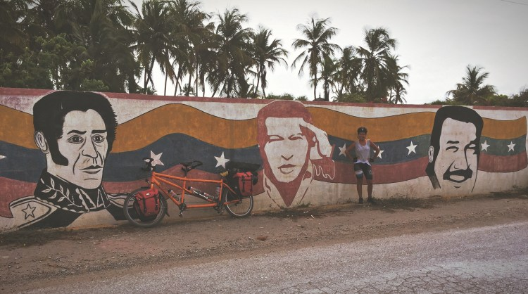 A woman and a tandem bicycle leaning on a wall with paintings of Hugo Chavez, Nicolas Maduro and Simon Bolivar