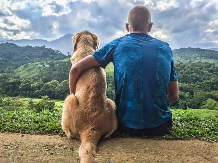 a man hugging a dog in the mountains