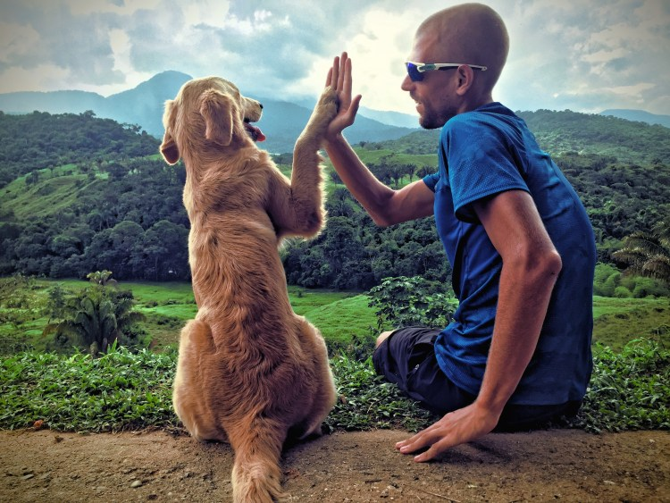 A man giving a high five to a dog in the mountains in South America