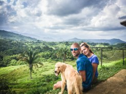 a happy man and a woman with a dog in the mountains during cycling adventure through South America