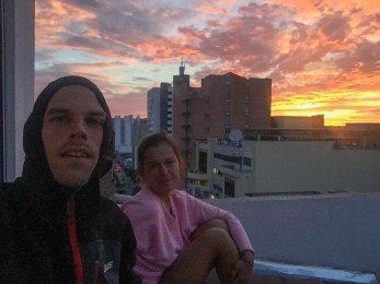 a man and a woman during a sunset in city