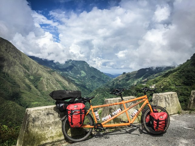An orange tandem bicycle with red panniers leaning on an asphalt barrier in the mountains