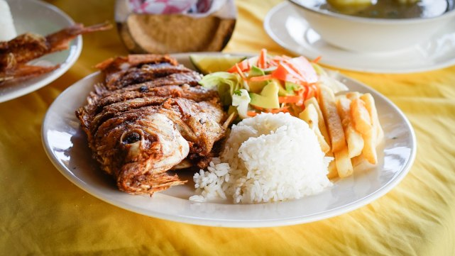 Mojarra with rice, french fries and salat on a plate