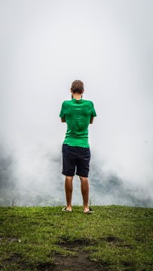 A man standing on a cloudy mountain