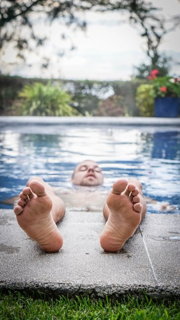 A man in a swimming pool with his feet out / The Art Of Serendipity While Traveling