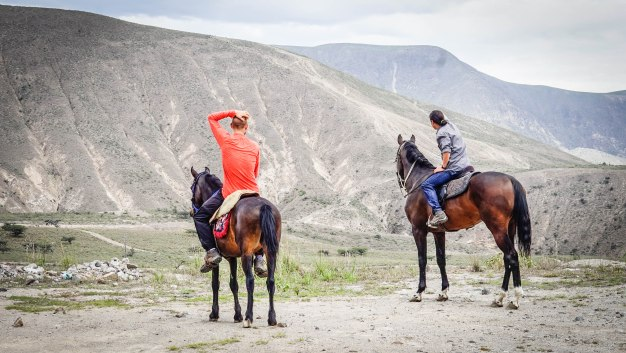 two men on horses in the mountains in Ecuador