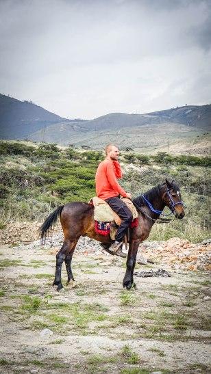 a blond man horseback riding in Ecuador
