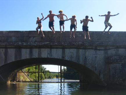 five boys and one girl jumping from a bridge into a river