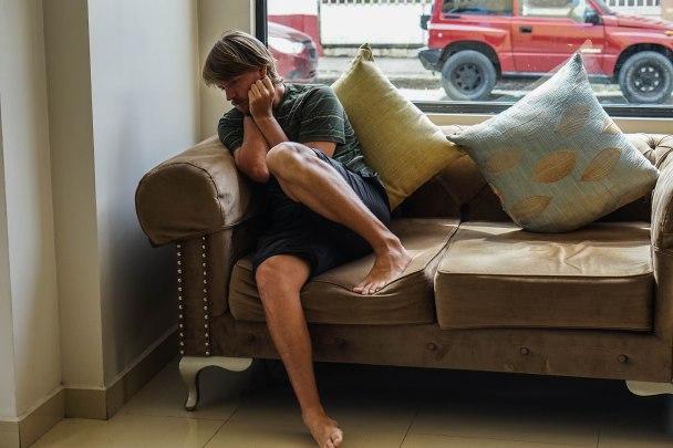 Man cowering on a sofa in Ecuador - Is Ecuador safe?