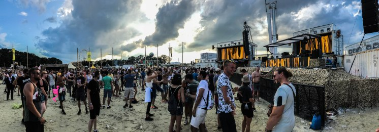 Many people dancing in sand at the Parookaville