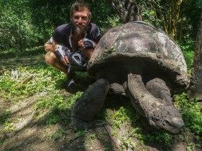 bearded man next to giant turtle in Ecuador