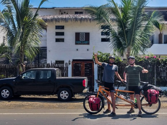 Two man on a tandem bicycle in front of the Sanctuary Puerto Cayo, Ecuador