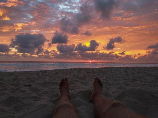 legs on a beach in Ecuador during sunset